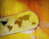 Outline map of world overlaid onto rusting paintwork of ship poster