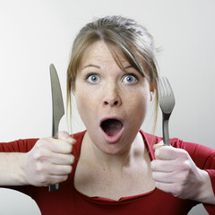 Surprised woman with fork and knife