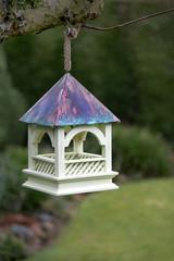 Wooden bird feeder hanging from garden tree