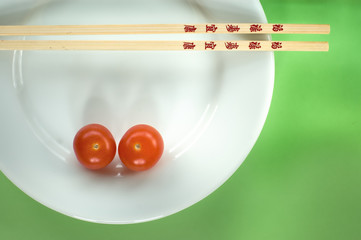 Two cherry tomatoes on a white plate with chopsticks