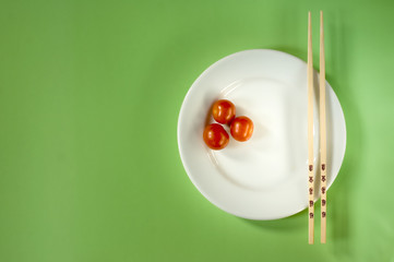 Three cherry tomatoes on a white plate with chopsticks