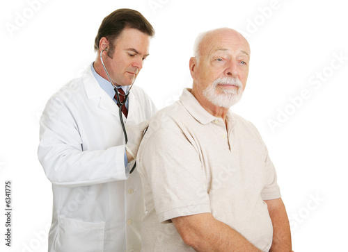 Doctor examining senior man.  Both have serious expression