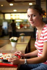 Frau isst im Schnellimbiss