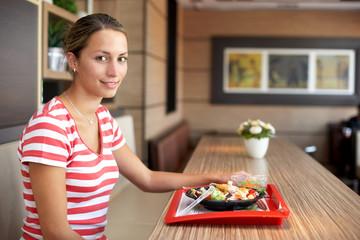 Frau isst Salat mit Schnellimbiss