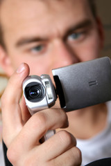 young man with digital video camera