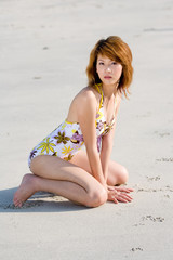 woman in swimsuit kneeling by the beach