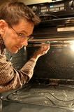 A man cleaning the inside of an oven in the kitchen. poster