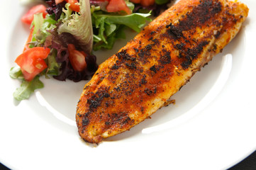 Whole seasoned fillet of white fish on mixed salad with tomatoes