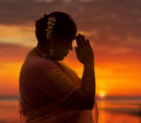Indian lady in saree doing the namaste greeting at sunset