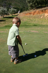 Toddler putting on the golf course on a sunny day