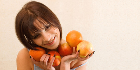 Young happy woman holding fruits to have a nice shape