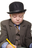 Boy in a suit and hat sitting at desk and writing