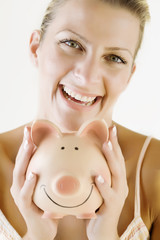 smiling female holding a piggy bank