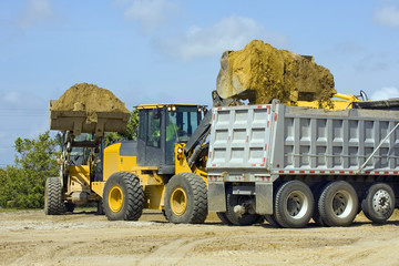 Front end loaders lining up to fill a dump truck