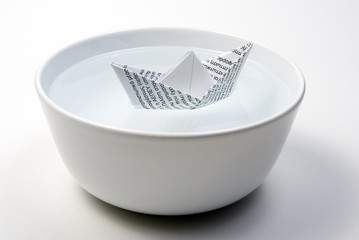 a paper boat in a bowl full of water