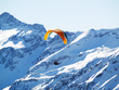 A flying paraglider in mountains in the winter.