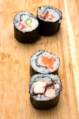 Four different sushi rolls on cutting board.