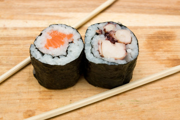 Pair of sushi rolls and chopsticks on cutting board.