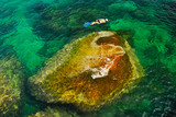 Snorkelling around a big stone in Transparent Emerald Waters poster