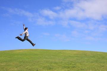 Happy man jumping on a beautiful landscape