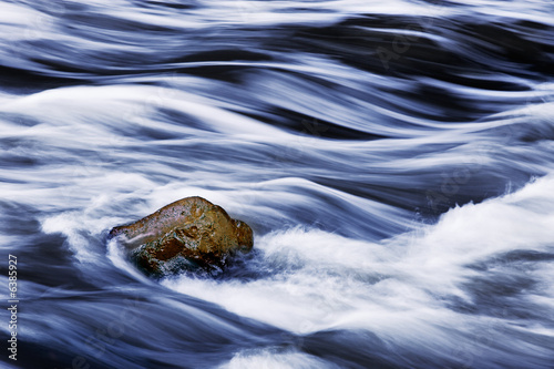 Water rushing by rock in river forming abstract appearance - 6385927