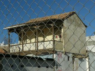 Casa con balcon a traves del cercado