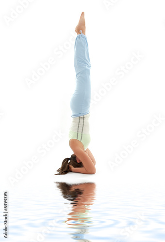girl practicing supported headstand on white sand