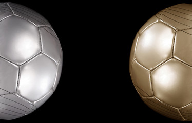 Close up of a gold and silver footballs on black