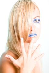 Blonde Frau mit Hand vor Gesicht und blauen Lippen