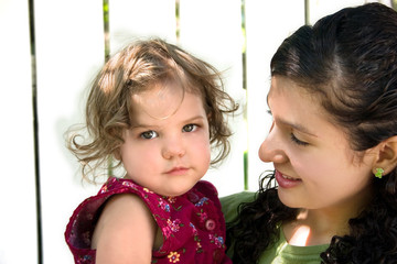 a young latino girl holding a little girl