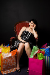 A beautiful woman resting on a chair after a shopping trip