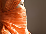 Close-up of a islamic woman covered with a orange veil poster