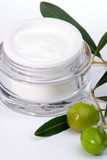 jar of moisturizing face cream and twig with green olives.. poster