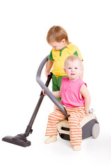 a small girl sitting on Vacuum cleaner and a small boy