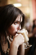 Beautiful young girl sipping coffee lattee. Shallow DOF. - 6408397