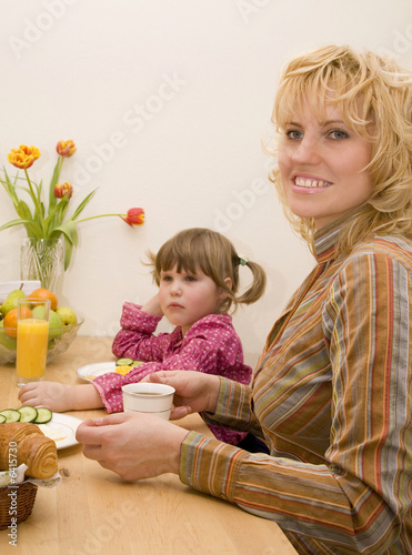 Woman and little girl have a breakfast