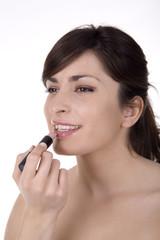 Woman doing makeup close up, studio shot.