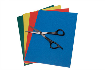scissors on colored paper on white
