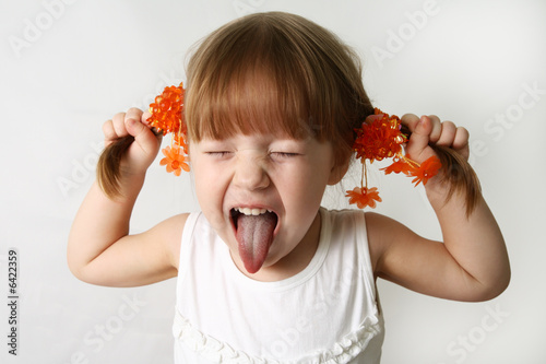 Little girl sticking out her tongue at the camera for fun