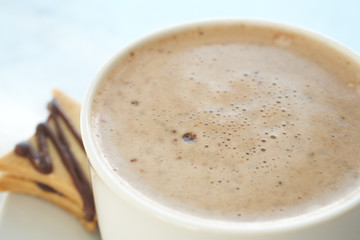 Fresh foamy cafe latte in white coffee cup on a silver