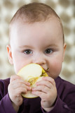 One year old caucasian baby boy holding an apple.