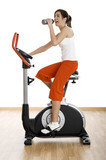 woman training on exercise bike at the gym and drinking water