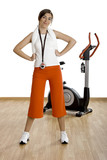 Beautiful female gym instructor with a exercise bike  poster