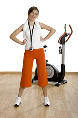 Beautiful female gym instructor with a exercise bike