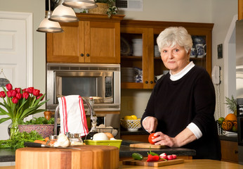 Mature woman cutting tomato.