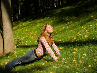Pretty girl doing exercises in the grass