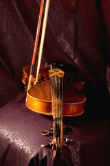 Old violin on dark backgrounds, focus on bridge