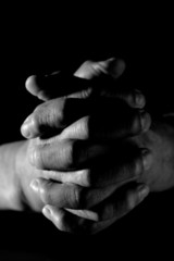 A closeup shot of praying old hands in black and white
