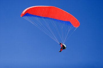 a paraplane flying high up in the deep blue sky