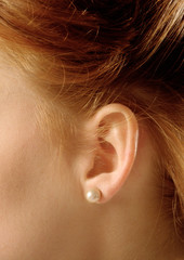 Woman ear wearing ear ring with pearl